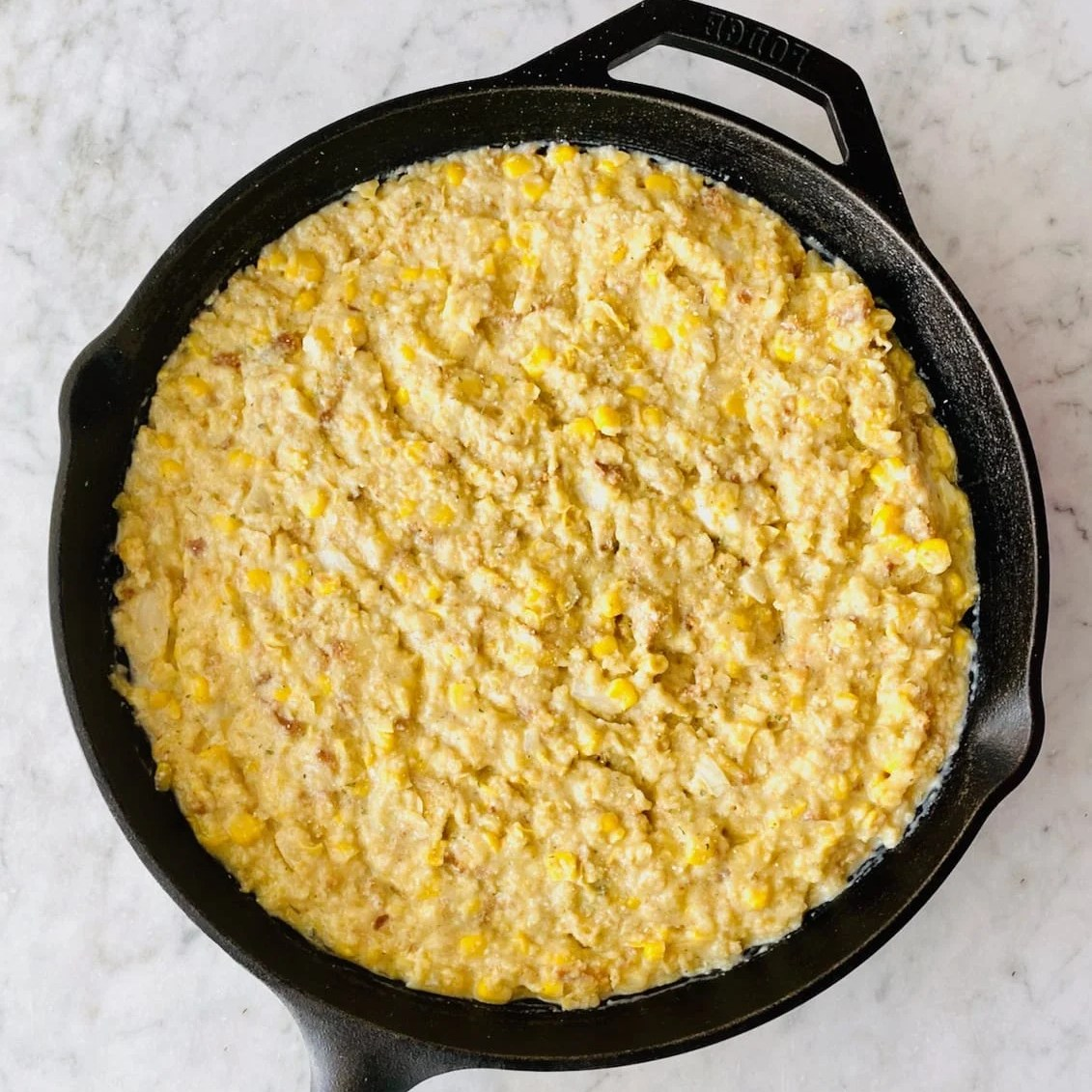 corn casserole in a cast iron skillet ready to go into the oven
