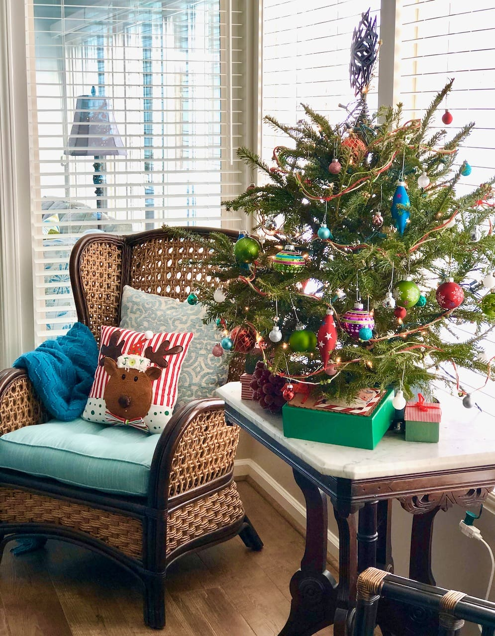 small tree decorated with shiny green and blue ornaments.