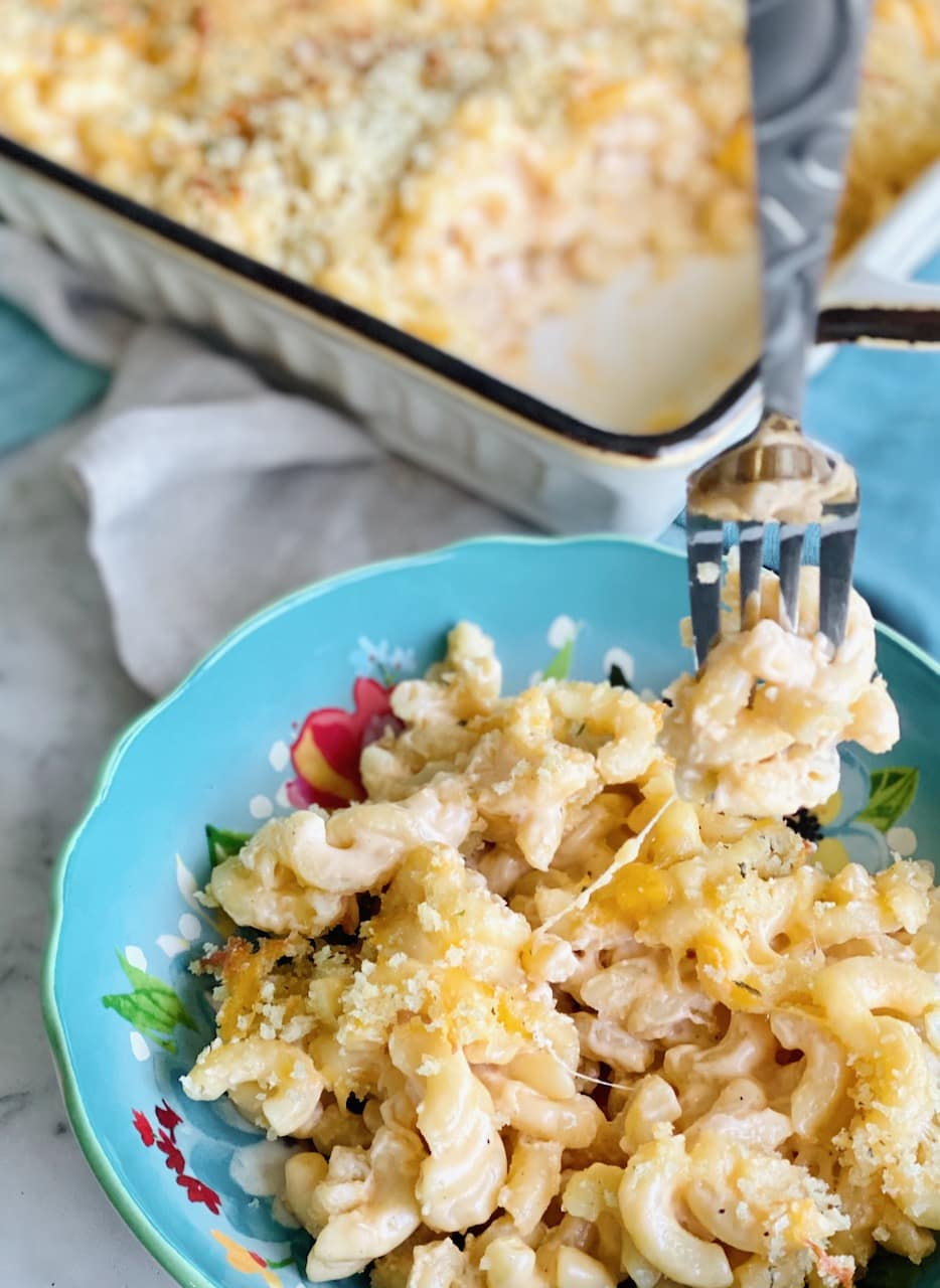 a fork twirling macaroni in a blue bowl.