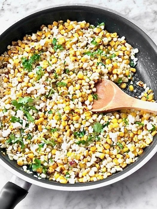 corn in a skillet with cilantro, spices, and a wooden spoon.