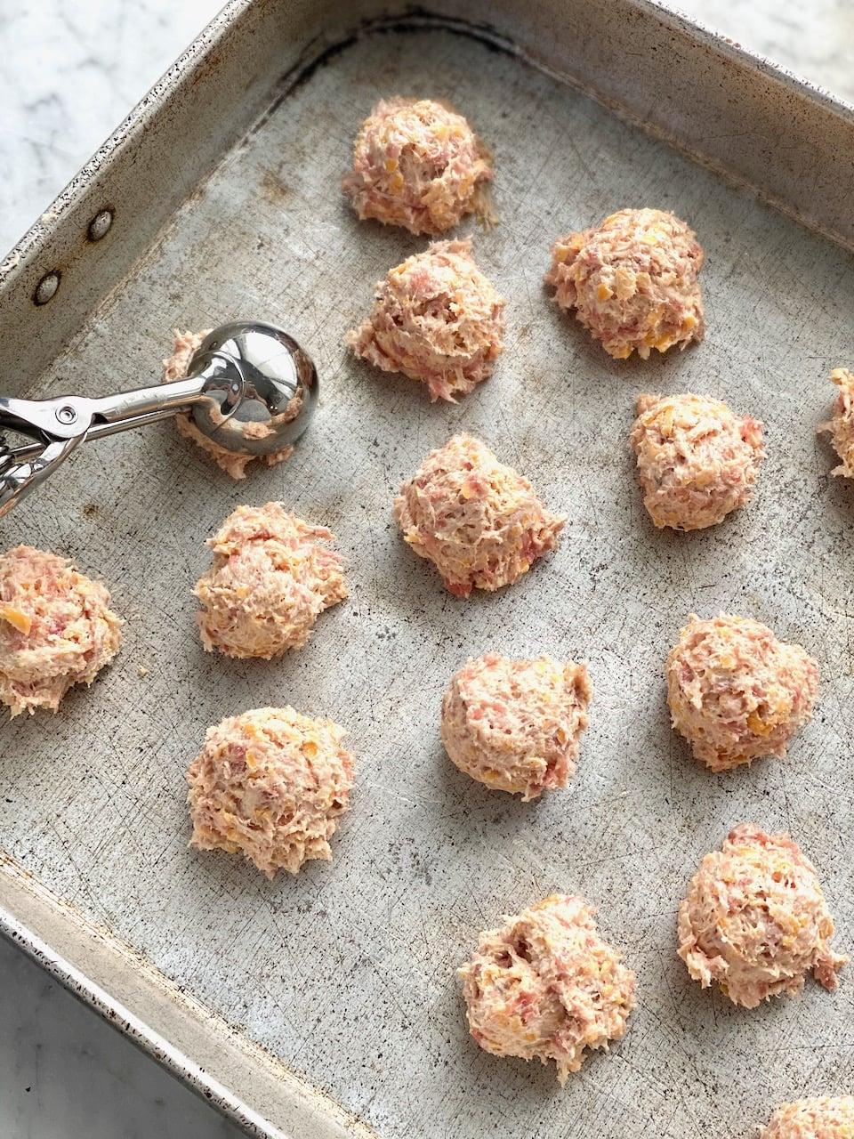 scooping sausage balls onto a sheet pan.