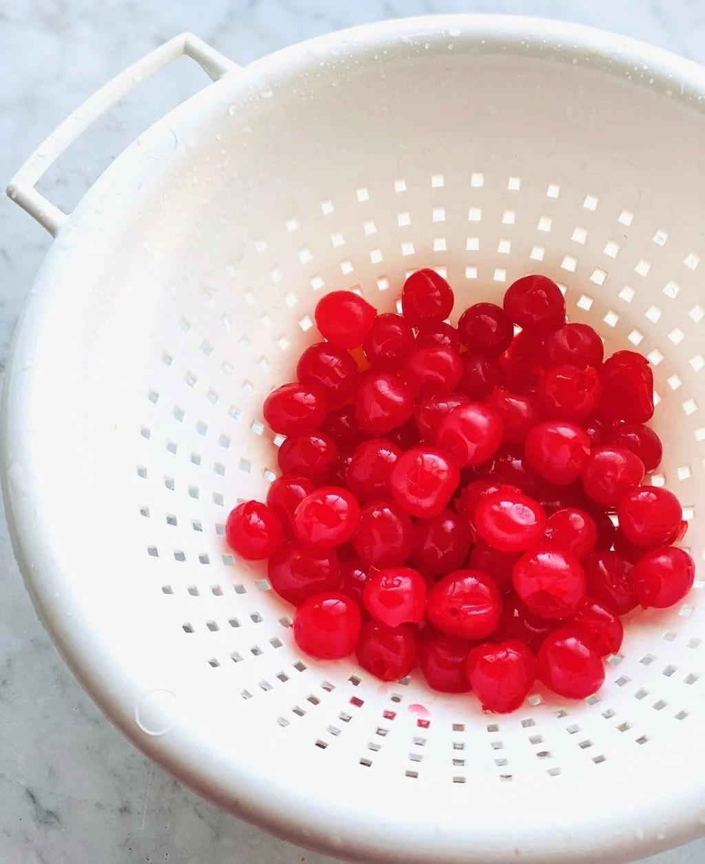 maraschino cherries in a white colander.