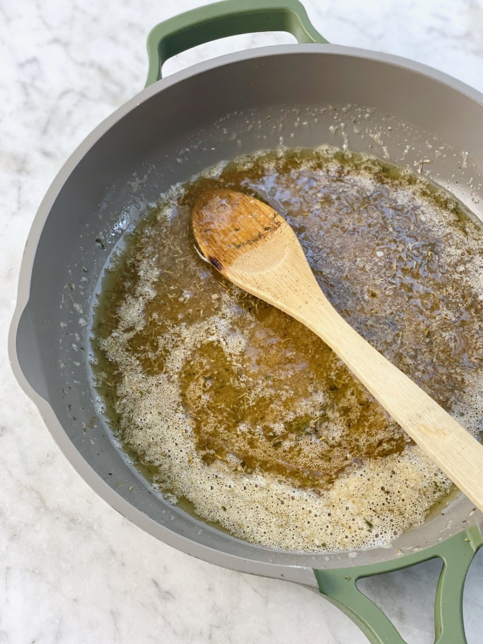 butter and brown sugar mixed with spices in a green frying pan.
