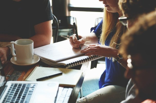 Four people meet in a coffee shop. One person writes in a notebook.
