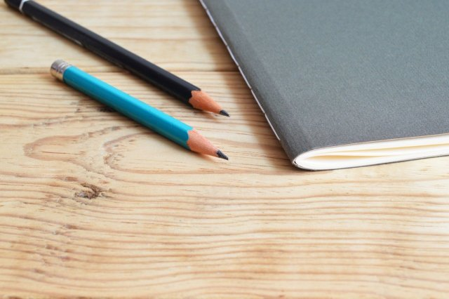 A blue pencil, black pencil, and gray notebook on a wood desk.