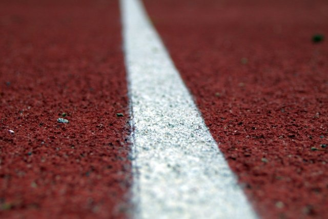 A white line on red ground. A symbol of the line in the sand that you need to draw to set deadlines and get motivated.
