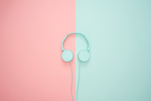 Blue headphones laying on a backdrop of pink and blue. One of the best productivity tips is to put on headphones and focus.