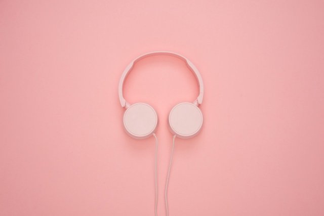 Pink wired headphones on a pink backdrop.