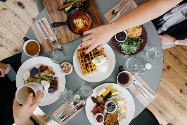 An assortment of food on a table. Many friends eating together - all taking a break at once.