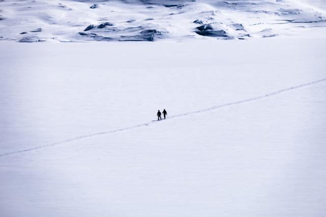 Two people walking through the snow.
