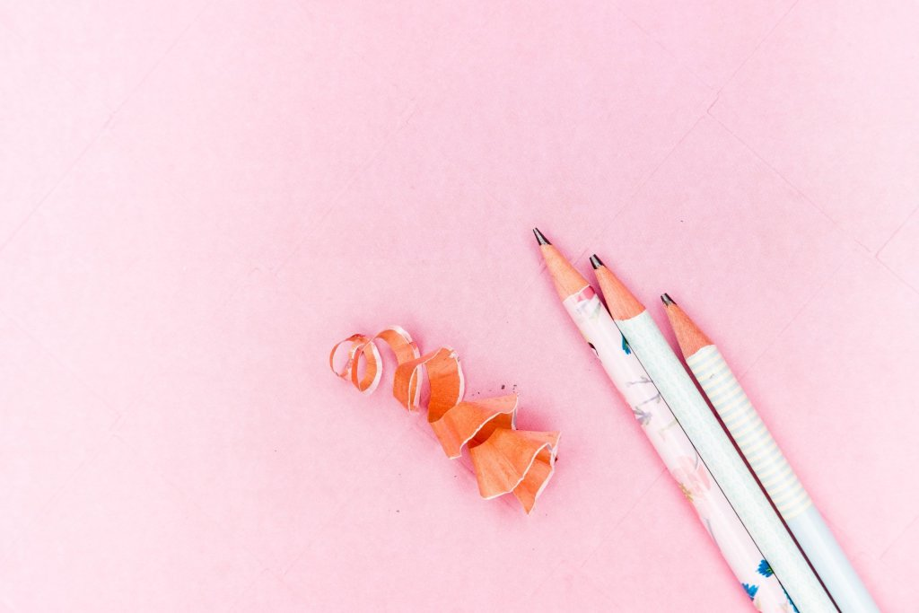 Pencils and pencil shavings on a pink background.