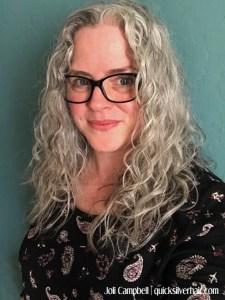 Image of joli campbell, gray hair, black frame glasses, and black paisley shirt