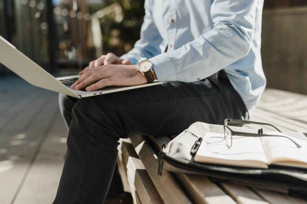 crop photo of man in blue dress shirt and black pants sitting on a wooden bench using laptop