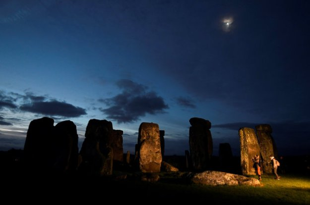Visitors take photos amongst the prehistoric stones of the Stonehenge monument at dawn on Winter Solstice, near Amesbury