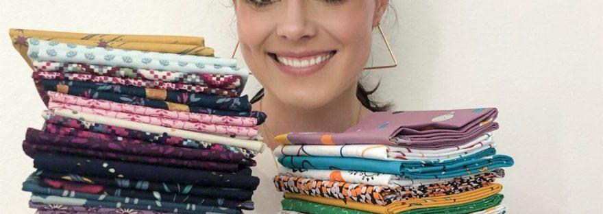 Elizabeth Chappell holding Fat Quarter bundles of fabric