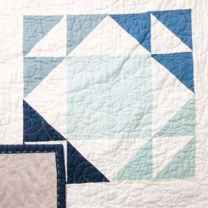 Snow Globes quilt center, with the quilt binding showing. It is hand quilted
