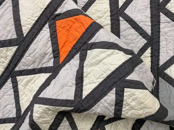 grey, black, and orange fabric triangles Cafe Tiles Quilt folded