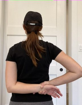 Elizabeth Chappell in a black hat and black shirt stretching her arms