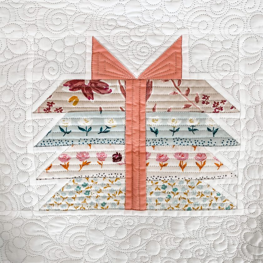 One 'Bundle Of Joy' Quilt block with a pink ribbon and blue and pink floral fabric.