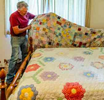 Roy Reichen shows off his family heirloom quilts