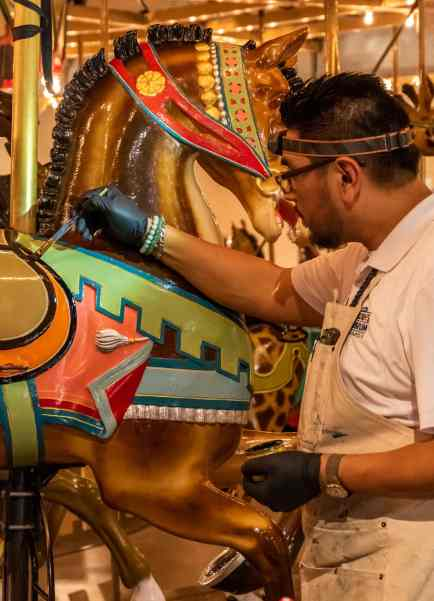 An artist touches up the paint one one of the carousel horses