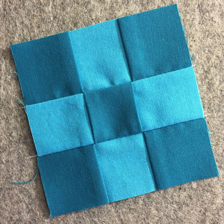A completed nine-patch unit in two shades of blue