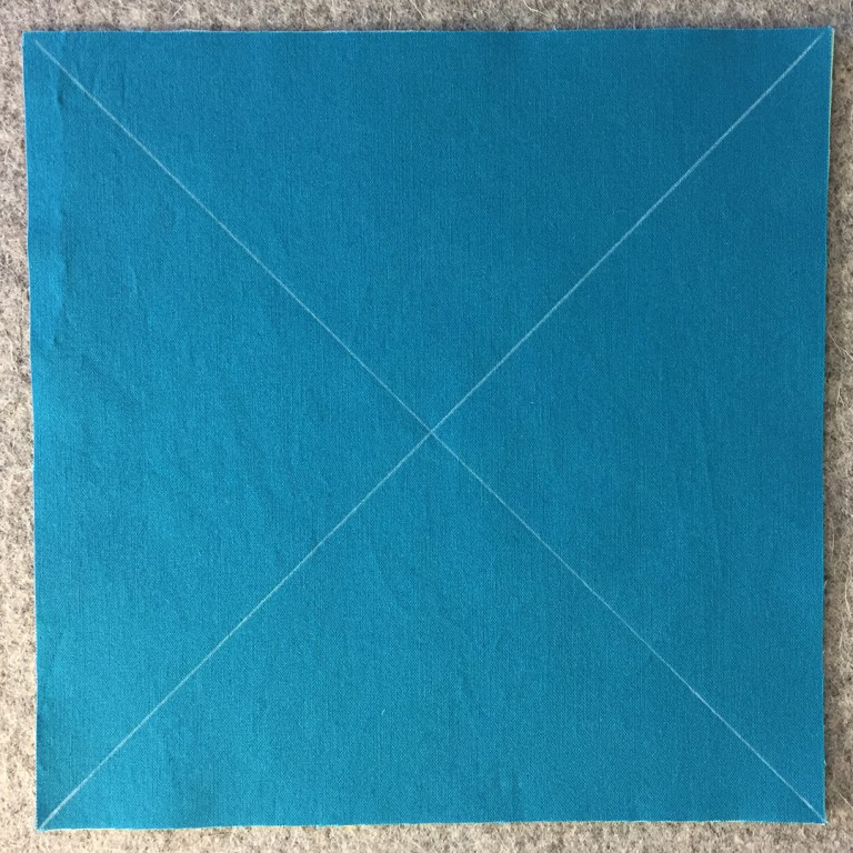 "An 8"" square of blue fabric marked with two diagonal lines forming an X from corner to corner"