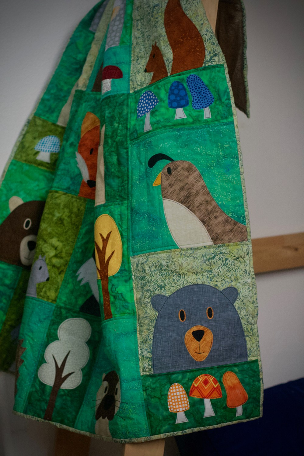 photo of a quilt hanging on a loft-bed ladder