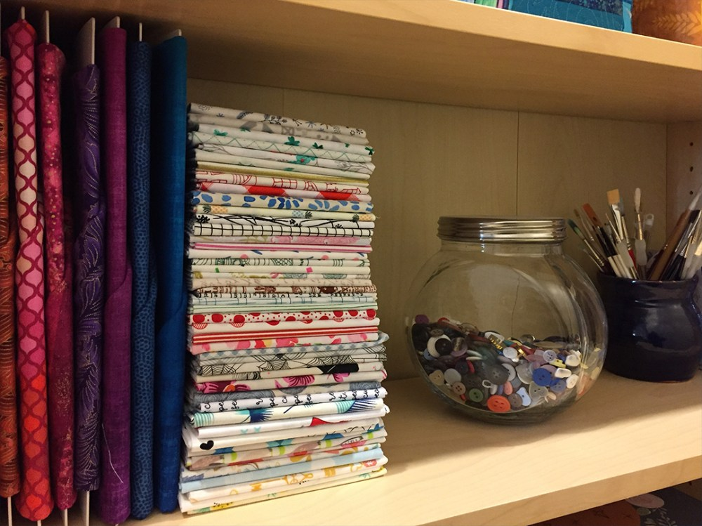 a stack of fabric and a glass jar half full of buttons