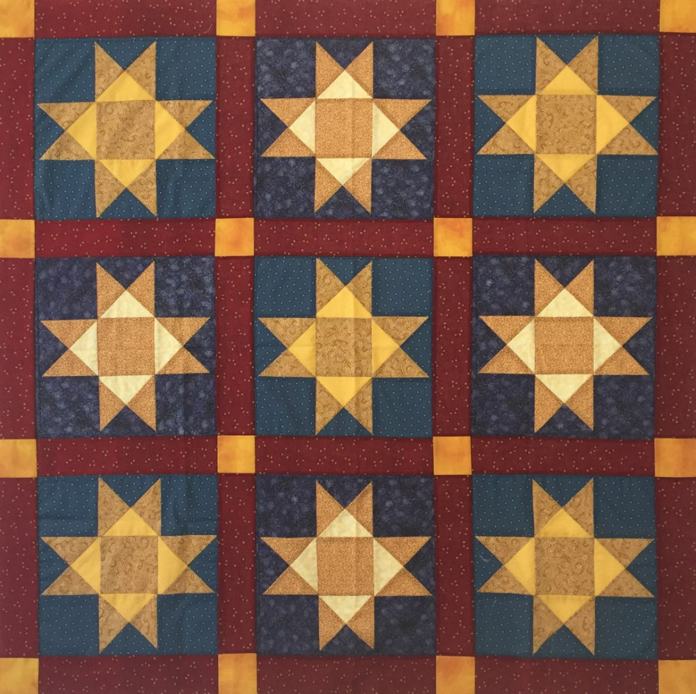 throw-sized quilt of yellow stars on a blue ground