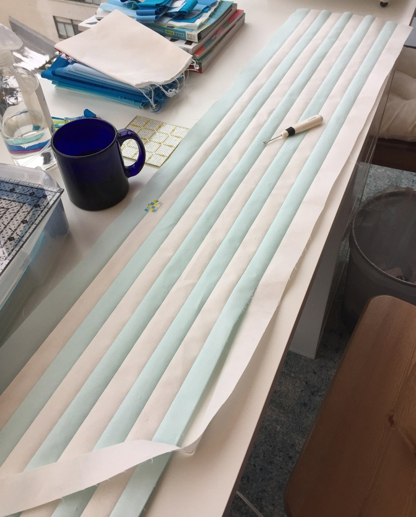 a long strip set and a seam ripper