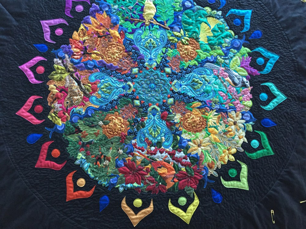 detail of quilt top showing meandering on the black background around the mandala center