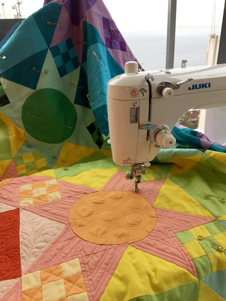 a quilt and a sewing machine showing a portion of the quilt