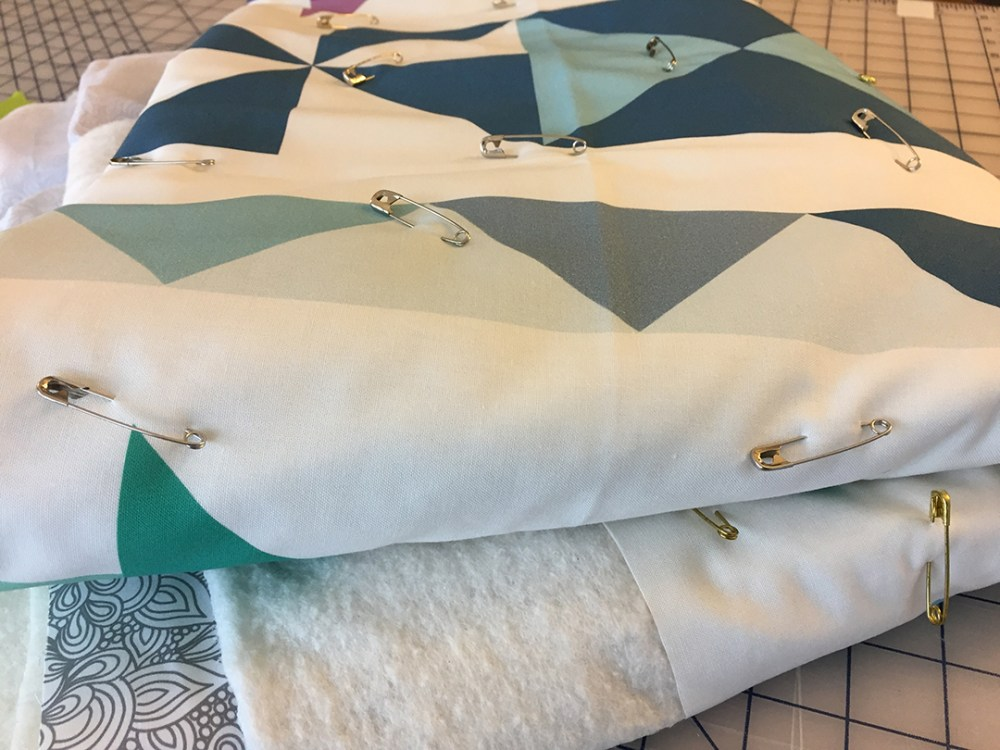 a pin-based quilt folded up in a stack