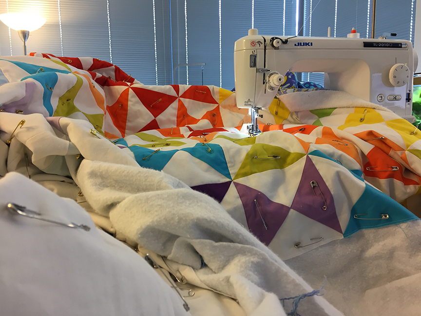 quilt draped over a table and ironing board to support it while quilting
