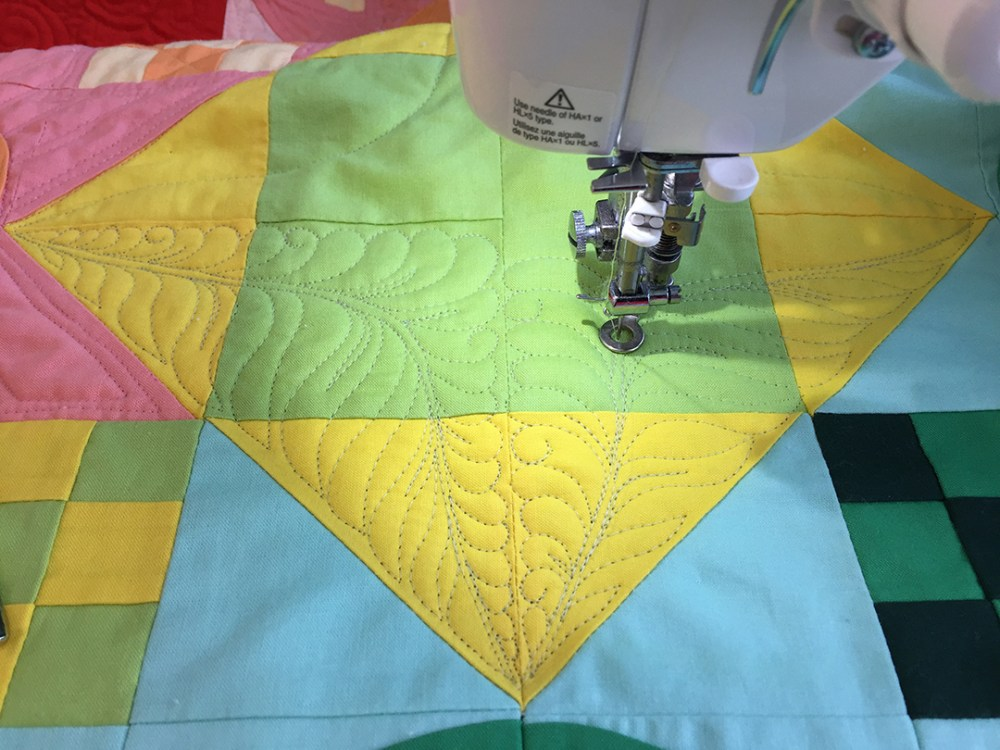 a colorful quilt loaded in a sewing machine and being quilted with a feathery design