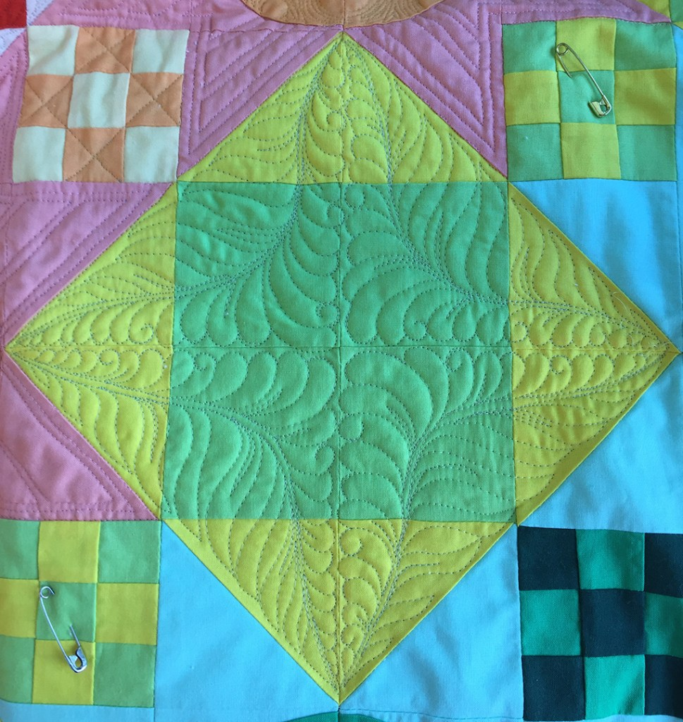 a yellow and green quilt block quilted with a design of feathers and ferns