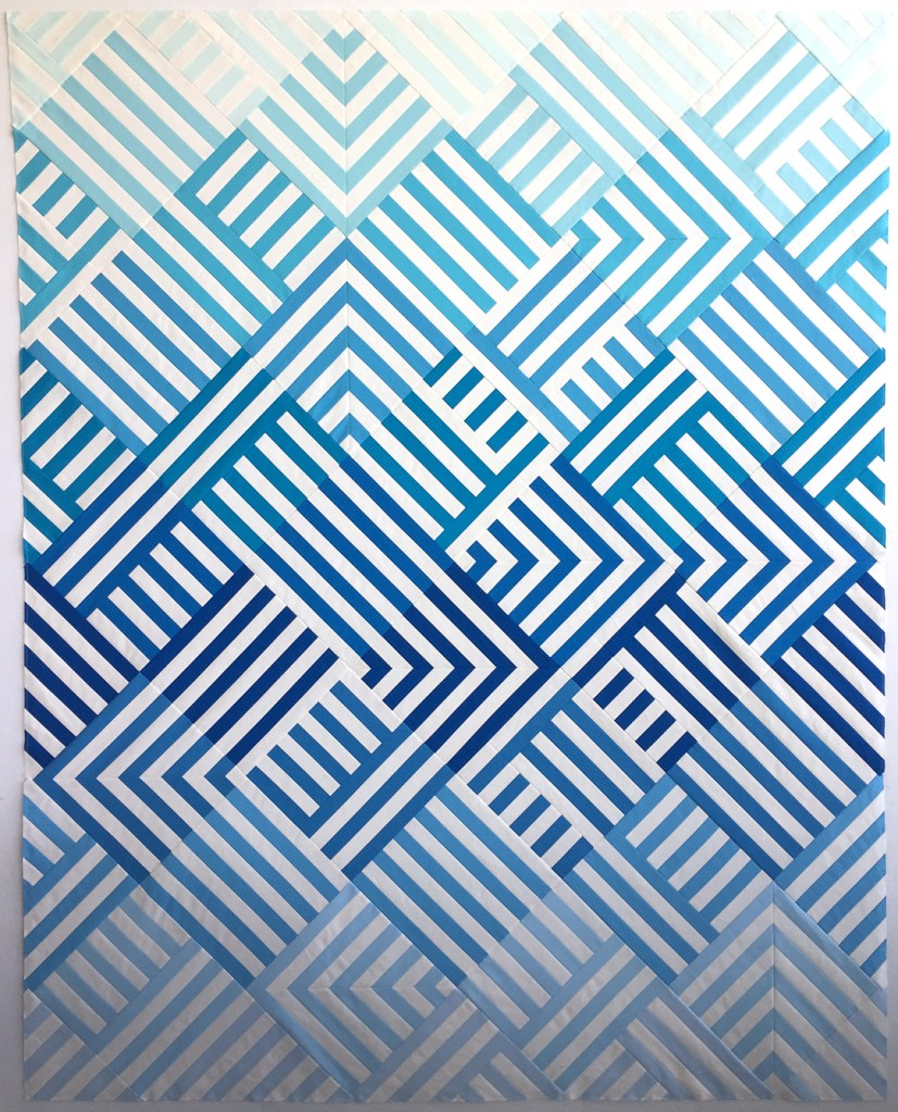 a quilt top made of white strips and strips of many blues