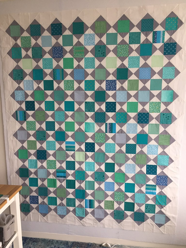 Teal and blue quilt blocks alternating with gray and white hourglass blocks on a design wall