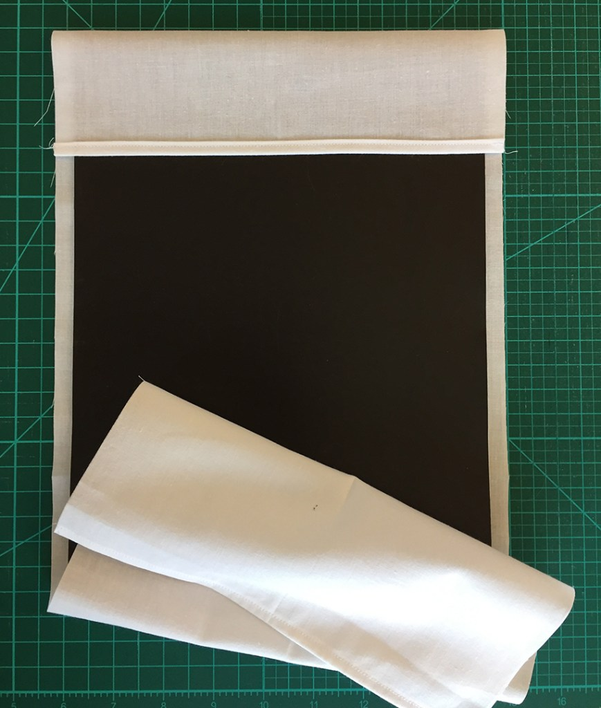 a piece of fabric being folded around a flexible magnetic sheet