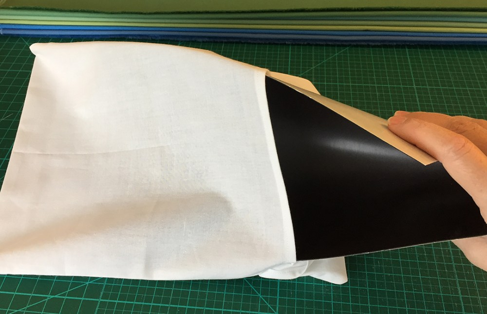 a flexible magnetic sheet being inserted into a fabric envelope