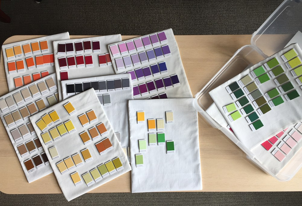 Colorful fabric swatch magnets attached to several fabric-covered magnetic sheets and a plastic box for storing them in