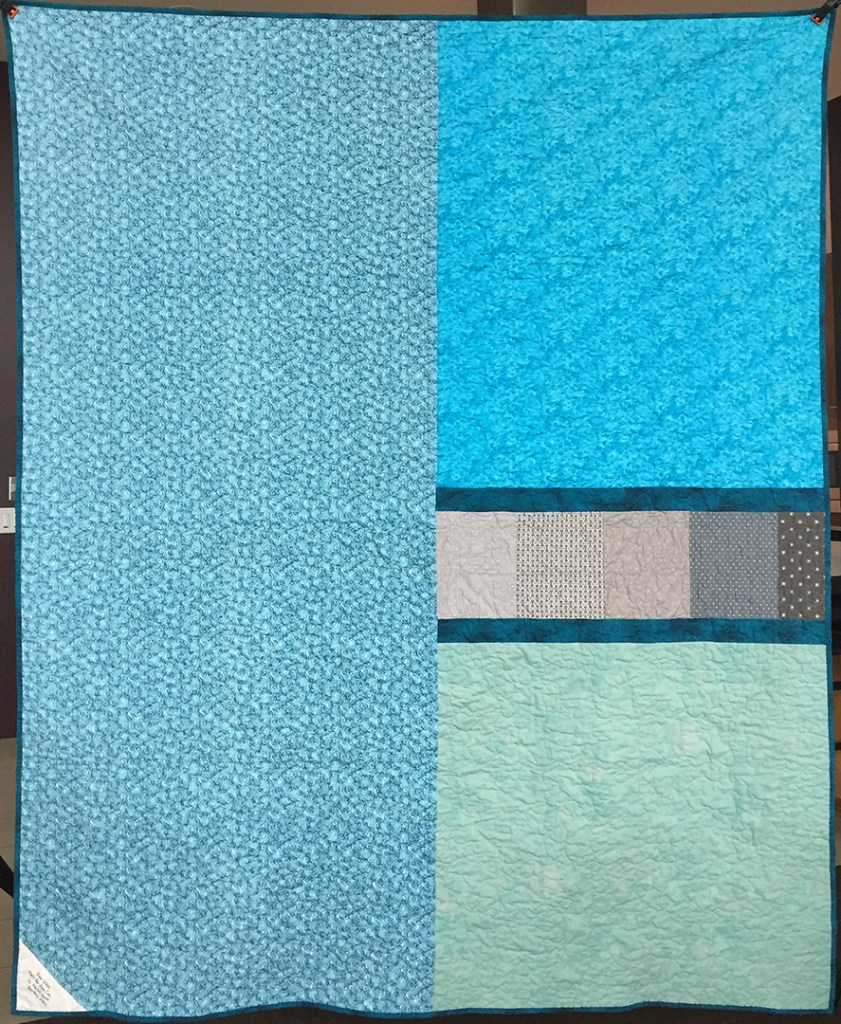 The pieced backing of a quilt in blues and grays