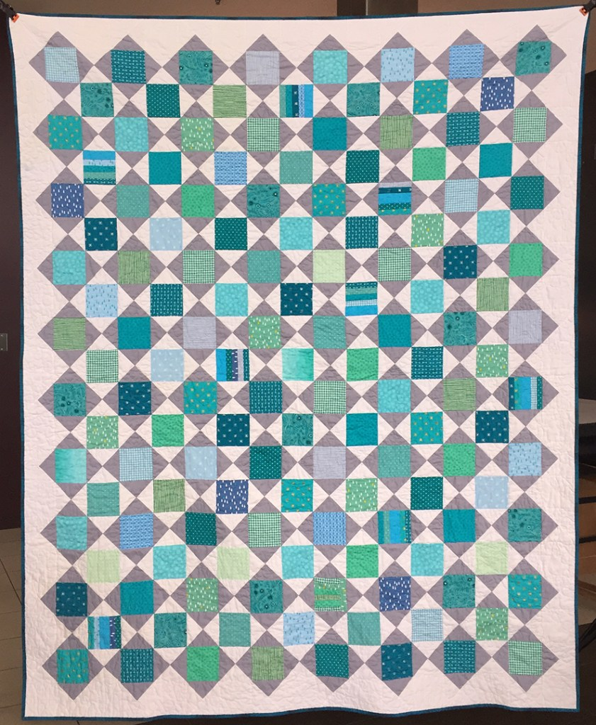 The front of a quilt with teal squares and grey triangles on a white background