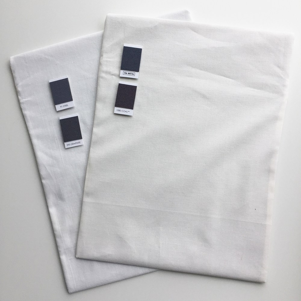 two fabric-covered magnetic sheets with swatch magnets on them, one white and one off-white