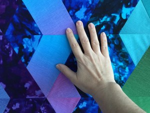 A hand on a blue quilt top