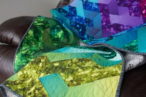 A colorful quilt draped over a brown easy chair