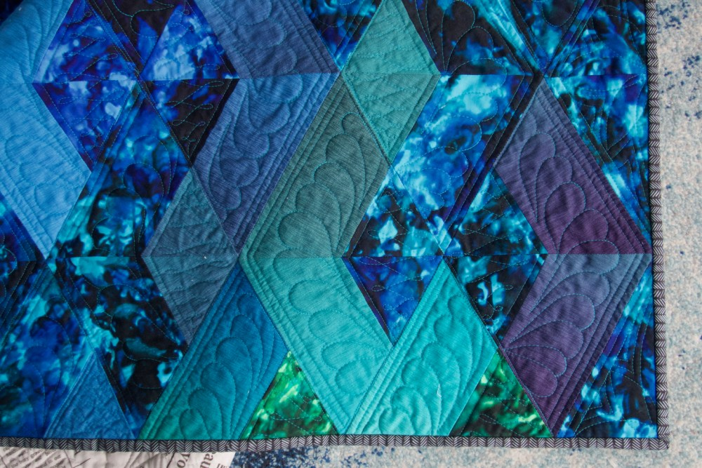 The corner of a quilt showing blue blocks and a striped binding