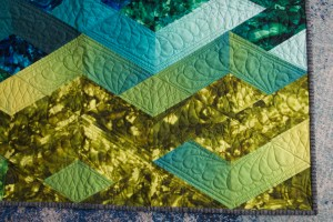 the corner of a quilt showing green diamond blocks and a striped binding