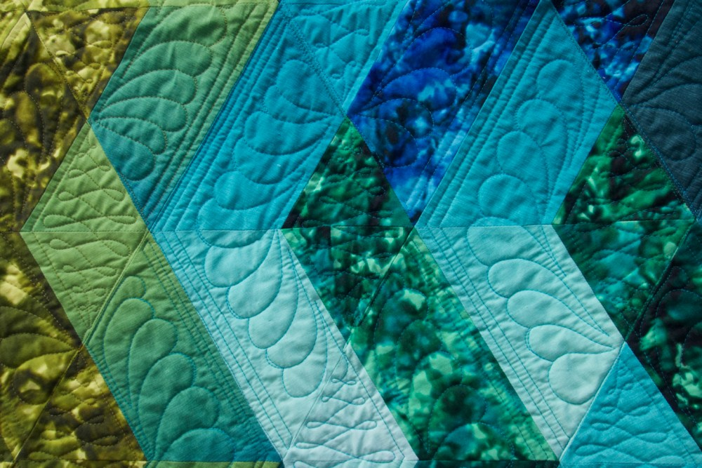 a close up of blue diamond shaped quilted blocks